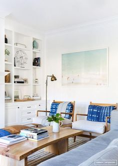 Crisp, clean bohemian meets midcentury living room with vintage Danish modern arm chairs, indigo mudcloth pillows, oversized beach print and floor to ceiling white built-in bookshelves. Love!