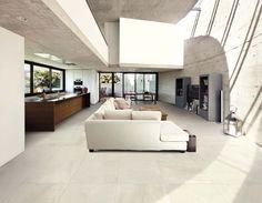 Loft Bianco #savoiaitalia #loft #cement #tile #madeinitaly #design #living #ceramic #sofa #white #modern #brown #grey #table #chairs #green #plants #lamp #light #window #books #vessels #kitchen #counter #space