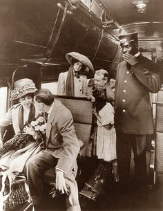 We wrap up Train Travel Week with this picture from 1909. It shows a group of passengers, and conductor on a train car. Travel used to be a big event.