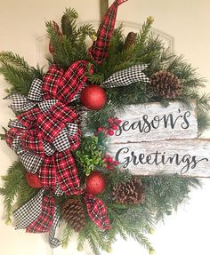 "Perfect for greeting guests into your home this holiday season! A charming Seasons Greeting wooden sign is tucked into a 14"" faux evergreen wreath. Accented with faux boxwood and berries. Gorgeous red, black & white plaid ribbon perfectly complement the classic gingham wired ribbon."