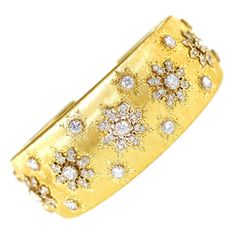 Buccellati Diamond Gold Cuff Bracelet. An 18 karat yellow gold cuff bracelet by Buccellati, the textured gold tapered cuff set with ornate openwork plaques set with 97 round diamonds weighing approximately 3.00 carats, gross weight 60.5 grams, length 6 1/2 inches, width 1 inch, signed M. Buccellati, stamped 750. A beautiful cuff bracelet by an iconic Italian jewelry firm known for their craftsmanship and metal techniques.