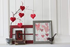 sweet, simple valentine mantle . . . paper hearts on dictionary paper, framed, fabric hearts hanging from a twig.  Love.