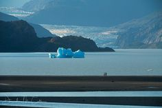 David M. Cobb Photography - Two people walk along a glaciated lake in Torres Del Paine National Park in Chile.