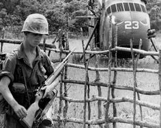 US Marine armed with an M14 walks in front a fence and Sikorsky UH-34 Seahorse with eyes painted on its nose, 1966.