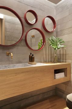 In this modern bathroom, multiple round mirrors with red frames act like an art installation, while a wood vanity and palm frond add a natural touch. #ModernBathroom #BathroomDesign #RoundMirrors