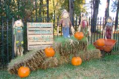 A painted pallet, scarecrows, and pumpkins sitting around bails of hay for your festive outdoor fall decor
