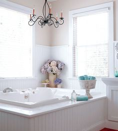 Modern Marble - I love the chandelier in the bathroom.  The lower portion of the bathtub was covered in white wainscoting to create unity throughout the bathroom.