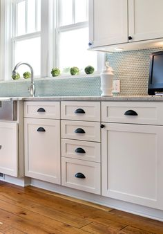 Love the sink and the white cupboards with black knobs