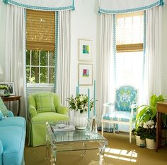 White drapes with simple braid trimmed cornice and bamboo shades.  Blue, spring green and white #CoastalStyle sitting room.  Acrylic coffee table.  Sisal rug. Palm Beach Style. Great fresh coastal style.  by Kelley Proxmire