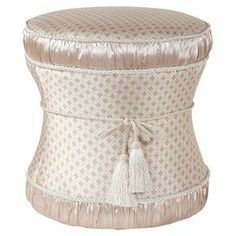 """Solid wood hourglass-shaped ottoman with rouched detail and a cord and tassel embellishment.  Product: OttomanConstruction Material: Wood and polyesterColor: PearlFeatures: Cord and tassel accentsDimensions: 19"""" H x 17"""" Diameter"""