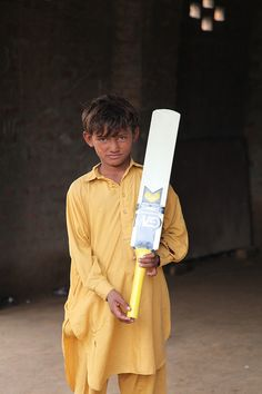 Boy from Lashkar Pur Children's Forum with new cricket bat in Pakistan.