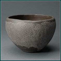 yama-bato: Junko Kitamura uses a sharpened bamboo stick to impress delicate geometric designs into the body of vessels like this one. She covers the piece with a dark slip (liquid clay) before the initial firing, after which she applies white slip to each indentation