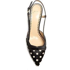 Polka dot ponyhair kitten heels featuring a pointed toe with ponyhair upper, black leather slingback with silver-tone buckle fastening, scalloped trim and a le…
