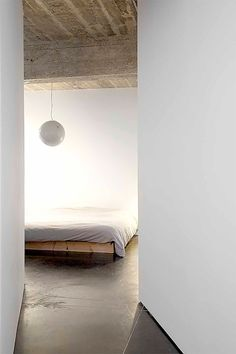 Rough concrete ceiling with smooth plaster walls and dark floor. C+C House by Ihoas+Ihoas.