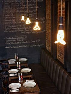 oo lala o-0 I like all of it. bench, table, chalkboard wall, light fixture, brick wall.