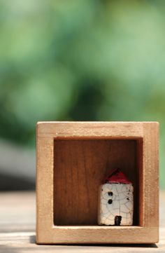Little ceramic house in shadowbox. - love the idea.  Maybe teeny boxes from pallet scraps?  Would be fun with tiny houses in any medium - polymer, ceramic, wood....