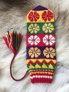 Anna-Kajsa Pavval's mittens highlight a common motif of the north – knitted flowers. She was a master of combining colors with these distinctive flowers. This pattern is based on a scrap of a mitten in Erika Nordvall Falck's Sami mitten collection. Knit Mittens, Mitten Gloves, Fair Isle Knitting, Hand Knitting, Knitted Flowers, How To Purl Knit, Hand Warmers, Handicraft, Knit Crochet