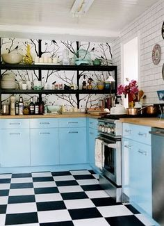 Admiring the bird wall and baby blue cabinets with the checkerboard floor