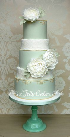 Pale sage green tiers with half height edible lace covered tiers and finished with sugar peonies.