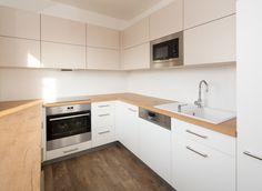 Kuchyň je v kombinaci bílé a krémové barvy a pracovních desek v dřevodekoru.