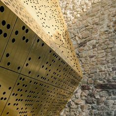 Hundreds of circular holes puncture a faceted bronze extension to a fortified museum in Rapperswil-Jona, Switzerland. By Swiss architects :mlzd Historical Architecture, Contemporary Architecture, Art And Architecture, Architecture Details, Gaudi, Exterior Wall Cladding, Perforated Metal, Metal Panels, Building Facade