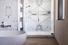 A bathroom design is clad in Margraf statuaria book-matched marble.