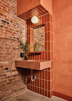 Russet tiling and plaster line the bathroom, matching the tones of the original brickwork.
