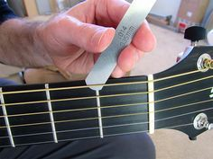 Use feeler gauges under the low E string until you find the one that slides under without lifting the string