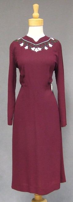 A classically styled 1940's cocktail dress in mulberry colored rayon crepe. Neckline has a lovely floral motif done in green and white beads
