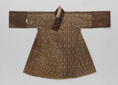"""""""A Jangot excavated from the romb of Lady Song of Eunjin, the wife of Jung, Eungdoo (丁應斗: 1508∼1572). Jangot was favored as an overcoat for women until late Joseon period. The coat is padded with cotton wool and hand quilted; outer layer is made of silk with a lotus and vine pattern. There are large armhole patches called Moo on each side, they come down along the side seam to help the ease of movement and retain the pleats of the skirt worn inside."""" at the Seok Juseon Memorial Museum."""