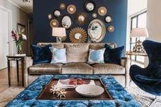 Fresh Faces of Design nominee SuzAnn Kletzien pulled bold blue into this living room with an accent wall, rich blue furnishings and blue-hued throw pillows. While the blues dominate the room, the surrounding white walls, neutral couch and gold-framed mirrors balance the look.