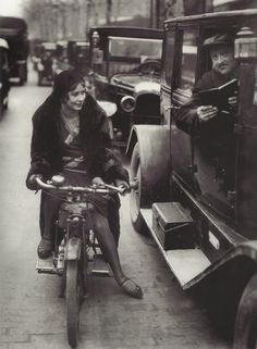 Jeune femme à moto demandant un renseignement à un chauffeur de taxi, Paris, années 1920-1930