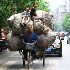 A collector rides a motor tricycle carrying bags of recyclable waste - and his  wife and son - along a street in Xi'an