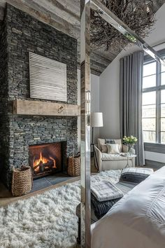 Restful country ski chalet bedroom is equipped with a gorgeous gray stone fireplace finished with a rustic wood beam mantel fixed below a gray and white abstract art piece mounted under a vaulted wood plank ceiling.