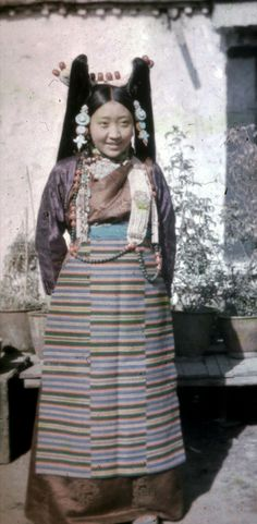 Lhasa | One of Tsarong's daughters, either Kate or Tess. She is wearing a Lhasa headdress (mutig patruk) decorated with corals and pearls, ear ornaments (agor) and a ga'u necklace. She is also wearing a silk chuba and decorated felt boots. | Tibetan.  ca. 1936 - 1950 | ©Hugh Edward Richardson