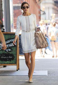 Olivia Palermo dans le quartier de Soho porte une robe blanche en dentelle, un sac à franges et une paire de ballerines