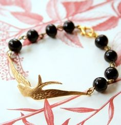 Soaring Swallow Charm Black Bead Bracelet  This simple and striking bracelet is Part cuff part vintage glass beads, made with a beautifully