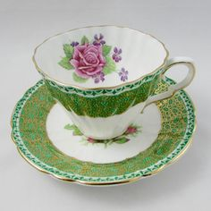 Beautiful green tea cup and saucer with large pink rose and gold trimming. Made by Gladstone and made in England. In excellent condition (see photos). Markings read: Gladstone Fine Bone China England Please bear in mind that these are vintage items and there may be small imperfections