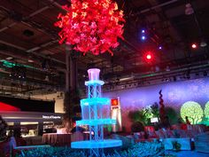 Giant flower orb hanging over a lighted neon display