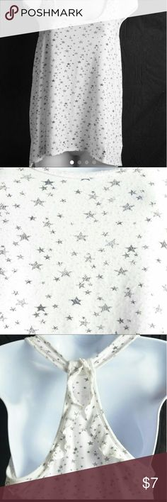 Medium White Converse One Star High Low Tank Top This is a very pretty tank top from Converse One Star collection that is solid white with different size, grey stars all over it. This tank top features a slight high low design at the bottom, and has a slight ruffled racerback design in the back.  There are no flaws with this tank top, and it is size medium. #converse #converseonestar #conversetanktop #highlowtanktop #stars #racerbacktanktop #ruffles #sizemedium Converse Tops Tank Tops