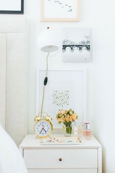 Inspiração para criado mudo estiloso: despertador clássico no dourado, flores, perfume e bandeja para jóias e acessórios.