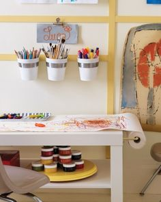 Creative Space Here, a compact arts-and-crafts spot is set up next to the bed. A gooseneck curtain rod was installed on an Ikea table to hold a roll of paper, with a slat of lattice securing the paper to the other end. A lazy Susan and wall-mounted caddies keep supplies organized