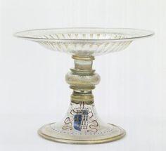 Coupe aux armes d'Anne de Bretagne, Venise, entre 1498 et 1514. Artiste: anonyme. Au XV°s, servis par une tradition séculaire d'échanges commerciaux avec l'Orient méditerranéen, les verriers vénitiens mirent au point une nouvelle composition du verre fondée sur une sélection de matières très pures aptes à produire un verre d'une transparence jamais atteinte (d'où son nom de cristallo, en référence au cristal de roche). Les souffleurs de verre de MURANO, en travaillant longuement le verre à…
