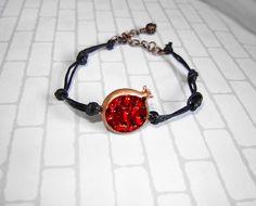 Pomegranate bracelet on black cotton waxed cord.