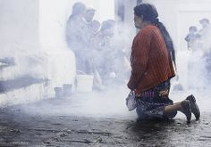 Entering San Tomas church by crawling in on bended knee. Mayan shamans burn candles and incense and perform their rituals on the steps to the church.  - Chichicastenango | Guatemala