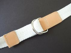 This vintage 1980s D ring belt is made from white duck webbing. Will fit up to a 33 inch waist. There are faux leather ends and silvertone D rings. It