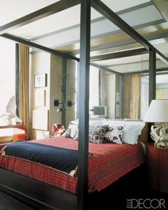 In the master bedroom of his SoHo apartment, designer Thom Filicia's ebonized-mahogany Tousey bed is covered with a vintage Indian silk bedspread from Varanasi and linens by Pratesi; the wall behind the bed is sheated in mirror-backed safety glass.
