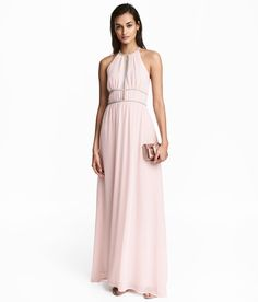 Long, dress in crêped woven fabric. Narrow-cut top with opening at front and short, narrow shoulder straps with fasteners at back of neck. Decorative metal-colored beaded trim at front and V-neck at back with concealed zip. Seam at waist and gathered skirt. Lined.