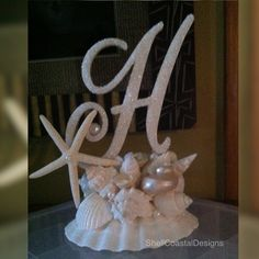 Who doesnt love a beach wedding? This listing is for a beautiful Beach Wedding Monogram Seashell Cake Topper, with a glass beaded embellished monogram letter, (custom letter A through Z), and a lovely white finger starfish. This can also be displayed in your home after your wedding celebration to remind you of your nuptials.  I started with a beautiful white Irish Baking Scalloped Shells, approximately 4 1/2 across, and then carefully placed white and pearlized and peachy colored shells…