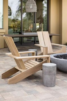 An outdoor fireplace surrounded by teak chairs